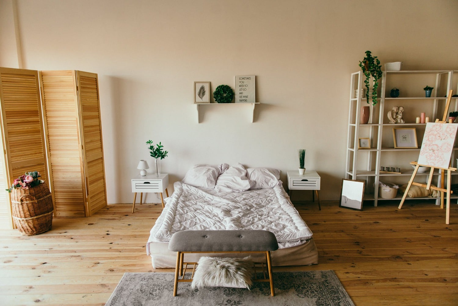 big bedroom area with bed, bench and shelves.