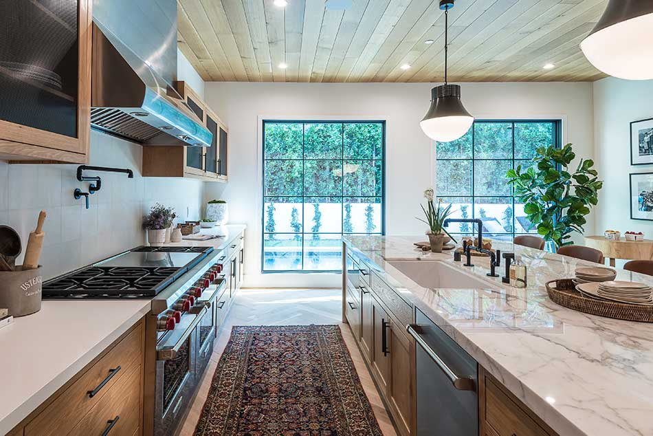 Kitchen with large windows and greenery.