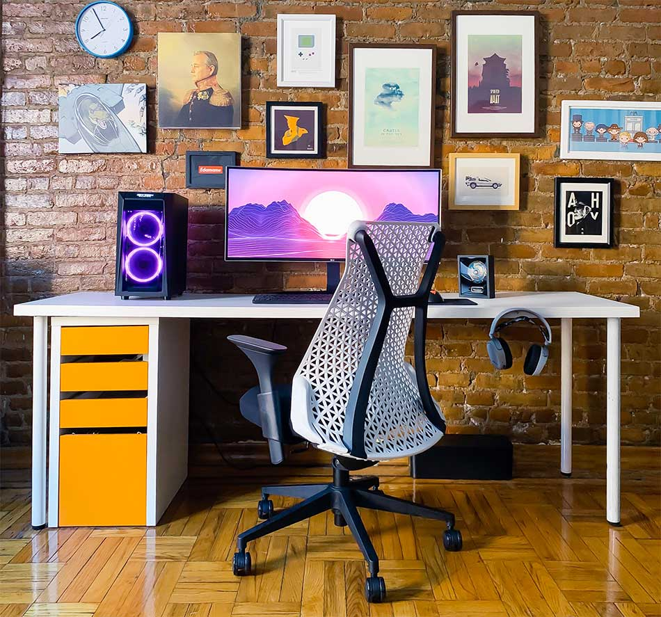 An ergonomic office chair with desk and wall gallery.