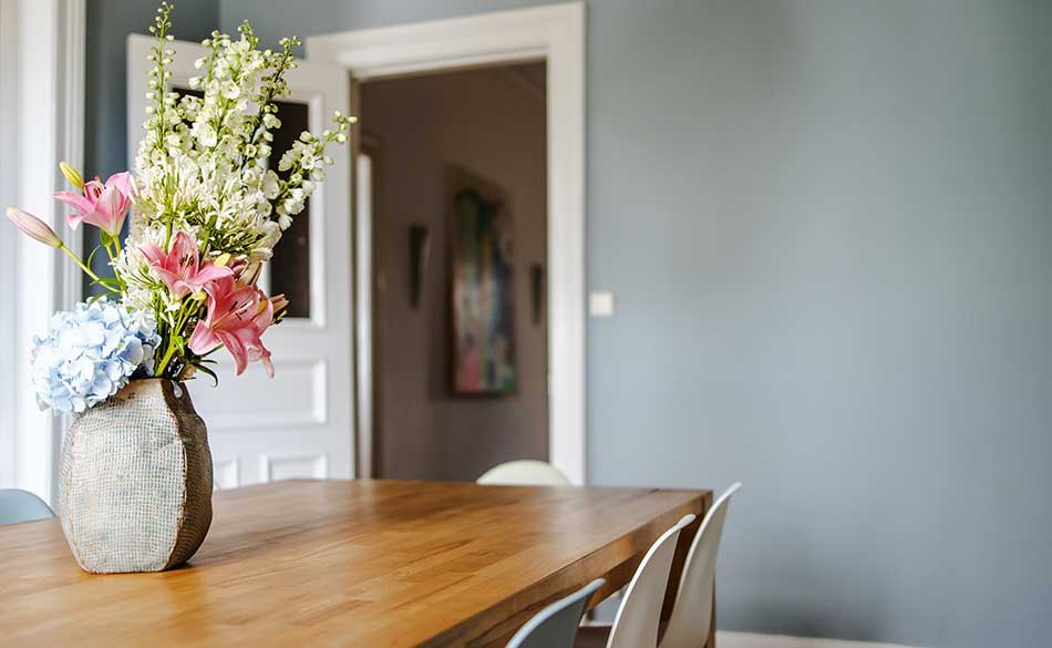 There are fresh flowers on dining table.