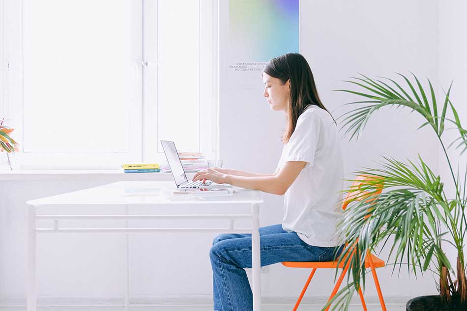 white home office with white desk, orange chair and woman.