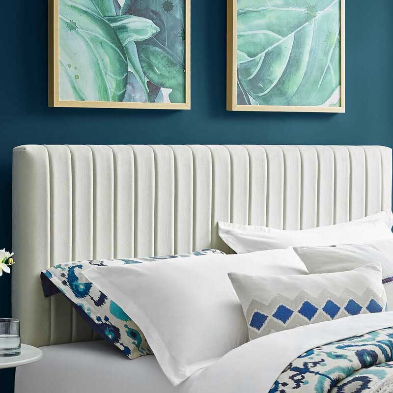 Upholstered panel headboard with dark blue wall.