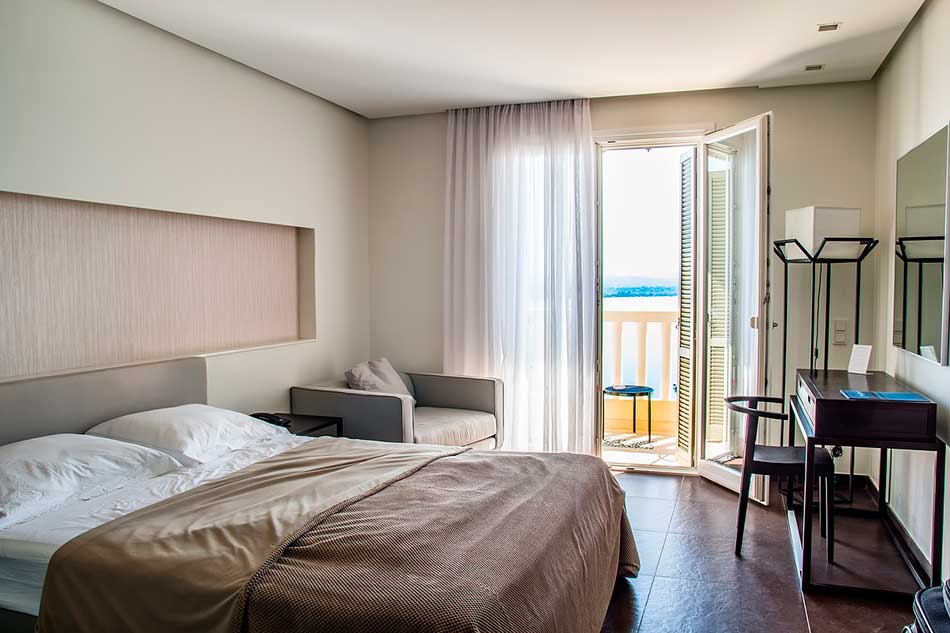 Hotel room design with small desk and balcony.