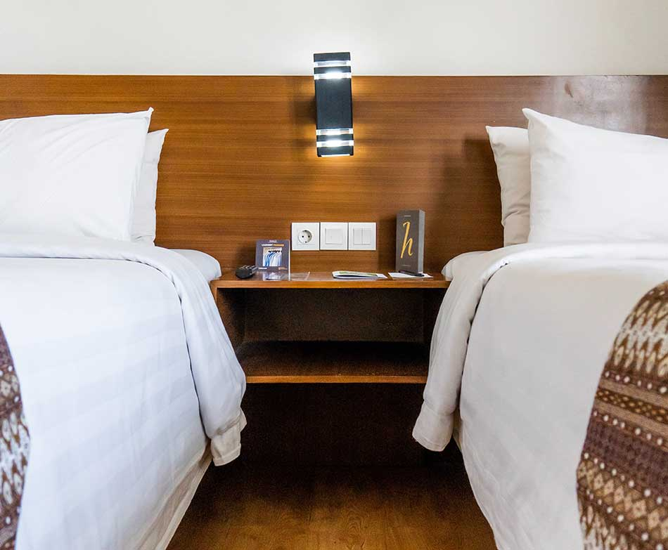 A nightstand between two beds in a hotel room.