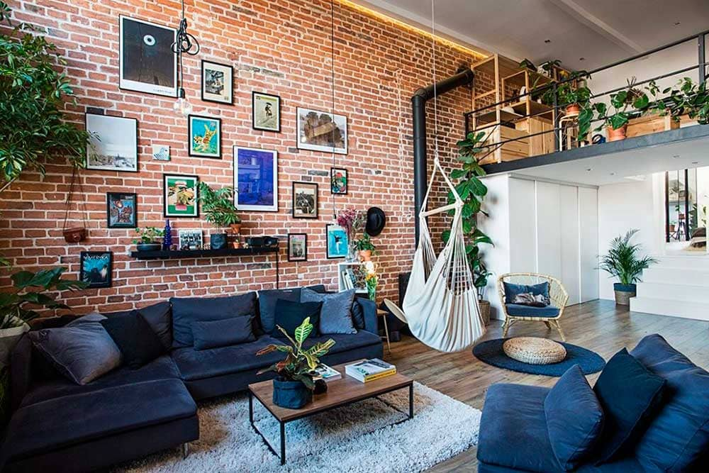 A loft apartment with hanging planters and dark blue sofa set.