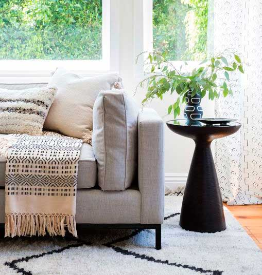 Black wooden side table and sofa in front of the window.