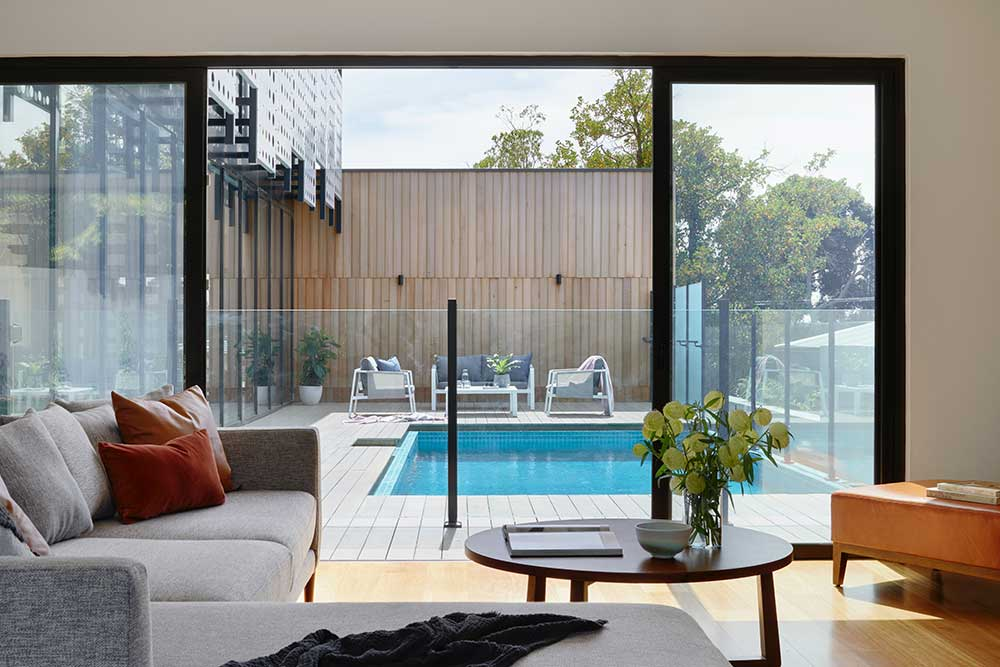 Sectional sofa against the window and pool view.