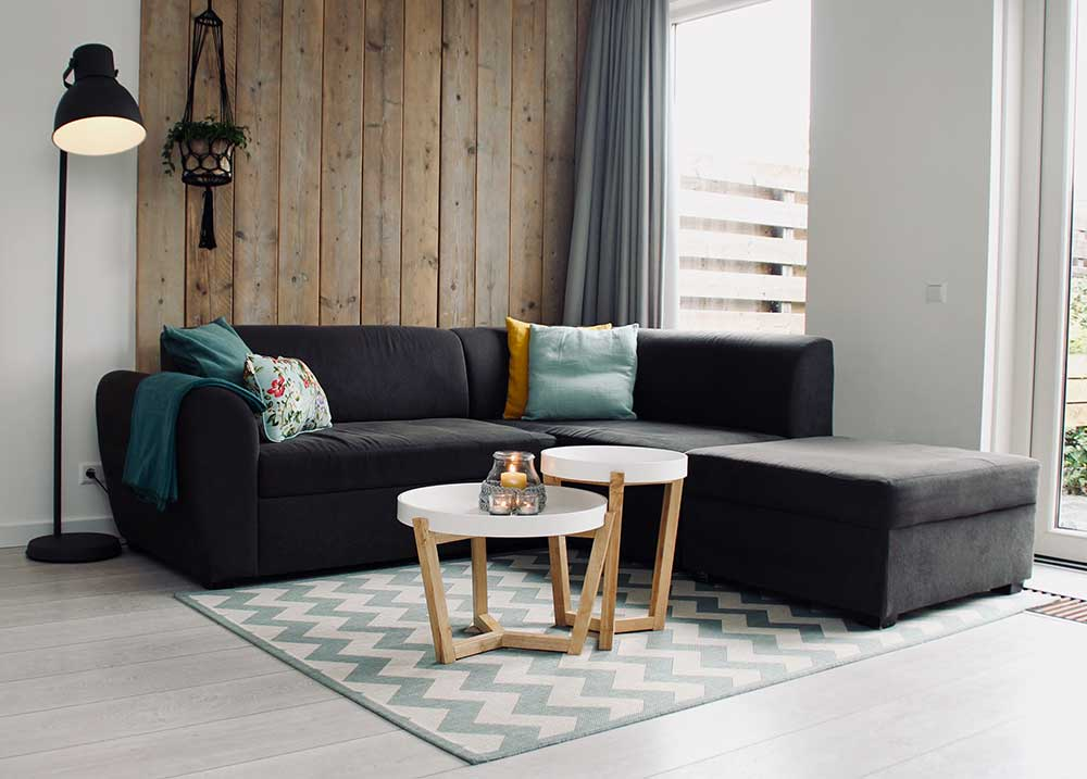Dark color sectional sofa arranged in the corner of the room.