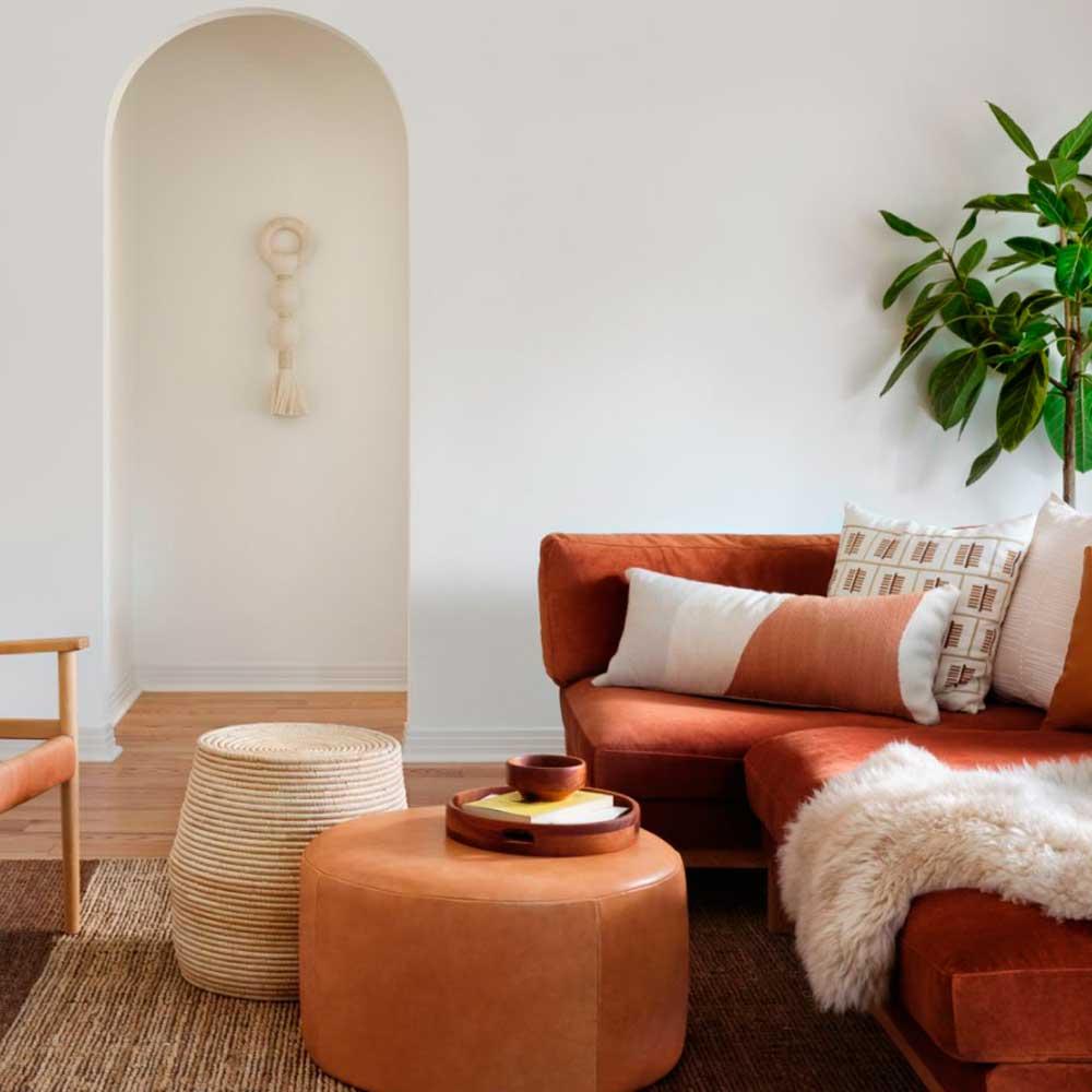 Artisan throw pillows arrangement with orange L shaped sofa.